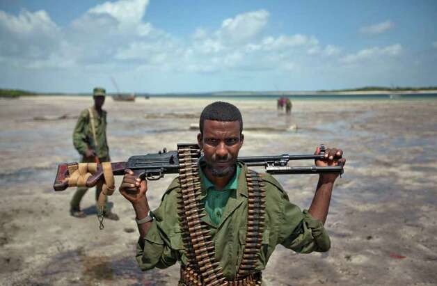 A member of a pro-government Somali militia patrols on the beach in the seaside town of Bur Garbo, Somalia, on Wednesday.  (AP Photo/Ben Curtis) Photo: Ben Curtis, ASSOCIATED PRESS / AP2011