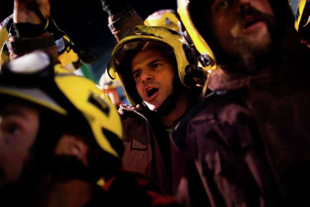 Firefighters take part in a protest against spending cuts in Catalonia's public services in Barcelona, Spain, on Wednesday. The euro is falling against the dollar on renewed fears that European leaders won't be able to solve the region's growing debt crisis. Spain's jobless rate stands at a 15-year high of 21.5 percent, the highest in the eurozone. Photo: Emilio Morenatti, AP