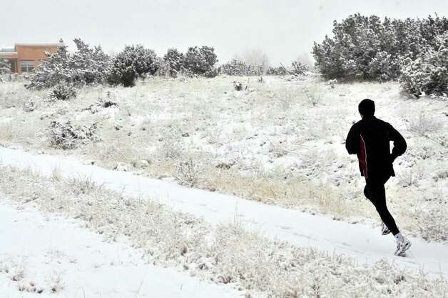 An Eldorado, N.M., jogger gets his morning run in through some snow on Wednesday.  Winter storm warnings and advisories are in effect as more snow and rain make their way across portions of northern and central New Mexico. Forecasters with the National Weather Service Photo: AP