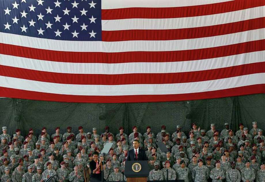 President Barack Obama, accompanied by first lady Michelle Obama, speaks to troops at Fort Bragg, N.C., Wednesday, Dec. 14, 2011. (AP Photo/Gerry Broome) Photo: Gerry Broome, Associated Press / AP