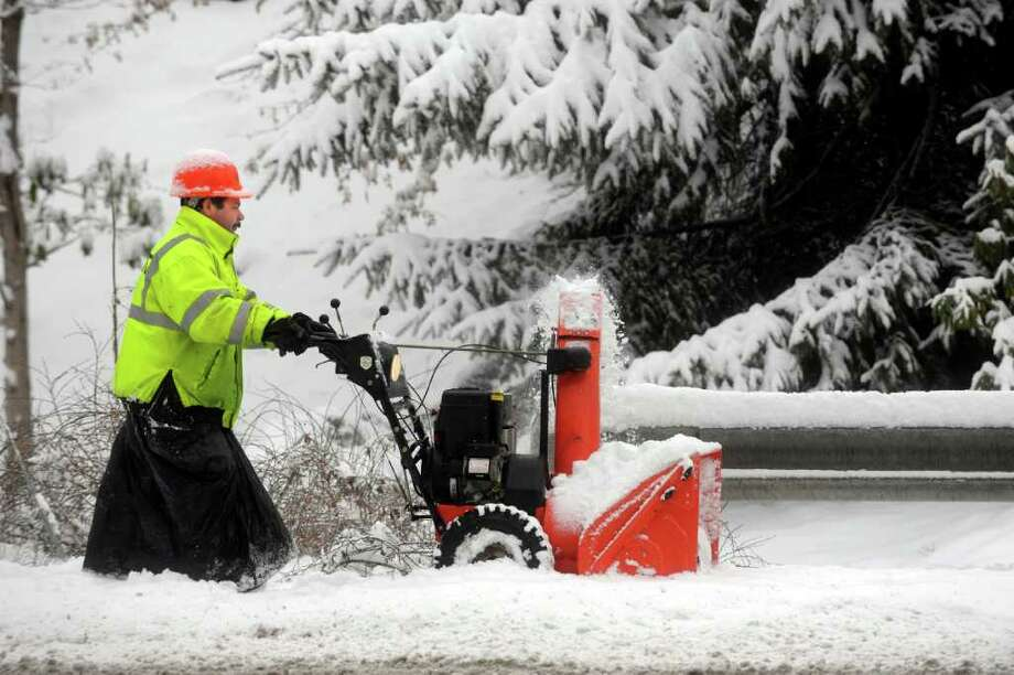 Adeulo Rua, working for Fred N. Durante Jr. Inc., blows snow off sidewalks near the Perrot Memorial Library in Old Greenwich, on Monday, Feb. 21, 2011. He is working for Fred N. Durante Jr Inc., blowing snow off sidewalks, near the Perrot Memorial Library in Old Greenwich  yesterday. He is wearing a garbage bag to keep dry. Photo by Helen Neafsey 2/22/11 GT photo = Highest In State. 7-inch Greenwich snowfall causes slippery communte. by Staff Reports Photo: Helen Neafsey, Greenwich Time / Greenwich Time