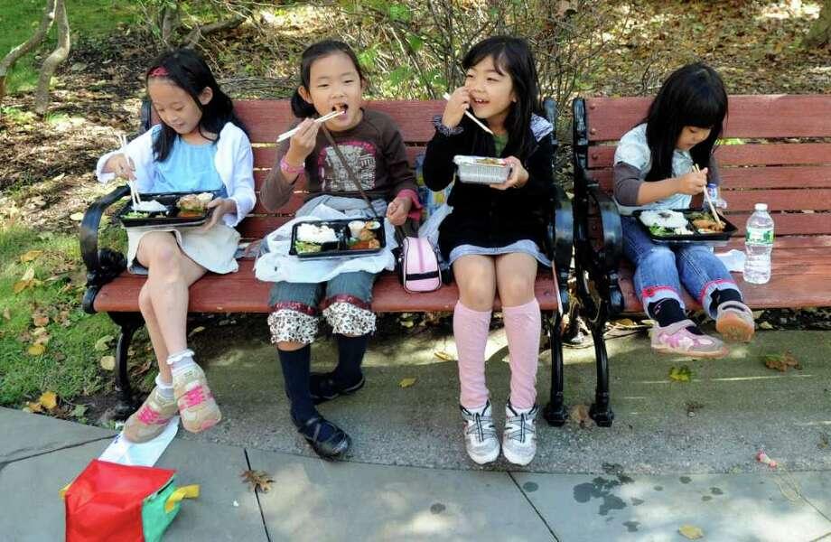 From left: Chihatsu Hasegawa, 8, Chihiro Nagayo, 8, Mako Yamamori, 7, and her sister Maya Yamamori, 4, have lunch at the Greenwich Japanese School Parent Teacher Association's Bunka Festival at the school on Sunday, Oct. 2, 2011. Photo: Helen Neafsey / Greenwich Time