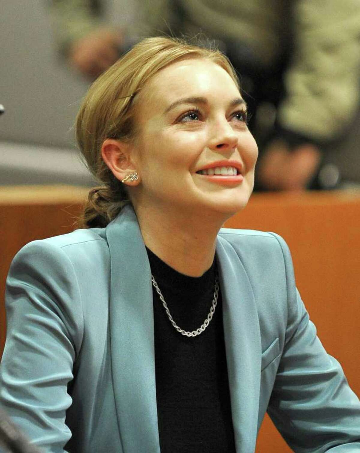 Lindsay Lohan smiles during a progress report on her probation for theft charges at Los Angeles Superior Court Thursday, March 29, 2012. A judge ended Lindsay Lohan's supervised probation on Thursday, giving the actress her freedom after nearly two years of constant court hearings and threats of jail. Lohan thanked Superior Court Judge Stephanie Sautner for her patience and let out a sigh of relief as she exited the courtroom after the brief hearing. (AP Photo/Joe Klamar, Pool)