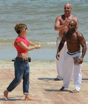 "US actress and singer Jennifer Lopez (L) tries a few movements with 'capoeira' (a Brazilian combination of dance and fight) performers at Playa de los Ingleses (Englishmen's Beach) in Montevideo on December 8, 2011. Lopez is in Uruguayan to make a casting for the tv reality show ""Q' Viva: The Chosen"". AFP PHOTO/Pablo PORCIUNCULA Photo: PABLO PORCIUNCULA, AFP/Getty Images / 2011 AFP"