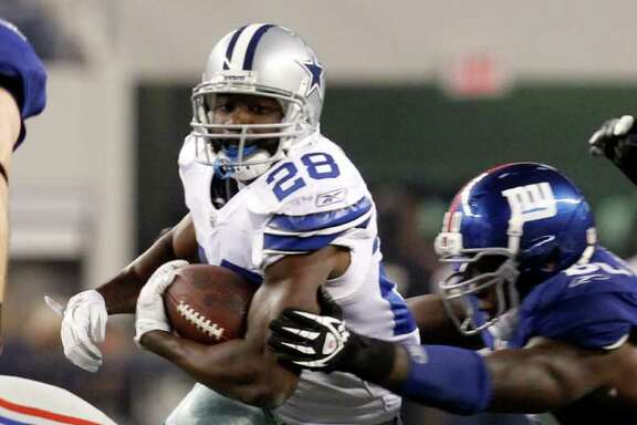 Dallas Cowboys' Felix Jones evades aNew York Giants' Jason Pierre-Paul during the first half of an NFL football game Sunday, Dec. 11, 2011, in Arlington, Texas.