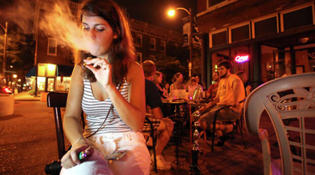 A young woman smokes synthetic marijuana or K2 at Petra Cafe and Hookah Bar in St. Louis, July 3, 2010. With a ban in early July signed into state law prohibiting possession of K2, investigators blame the herb in at least one suicide and has sent users to emergency rooms with elevated heart rates, paranoia, vomiting and hallucinations. (Dan Gill/The New York Times) Photo: DAN GILL, Wire / NYTNS