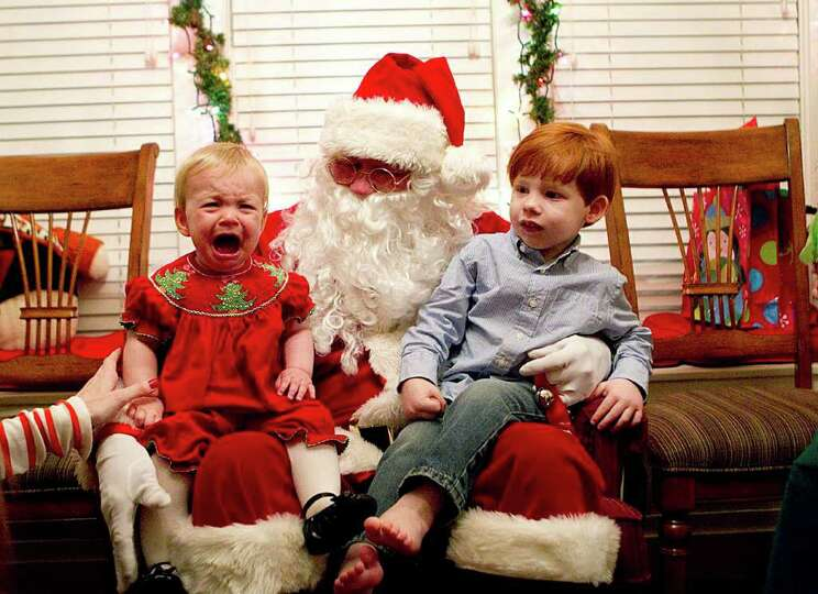 Caroline Hanson, 9 mo., greets Santa Claus with tears next to her brother Jack Henry Hanson, 3, at a