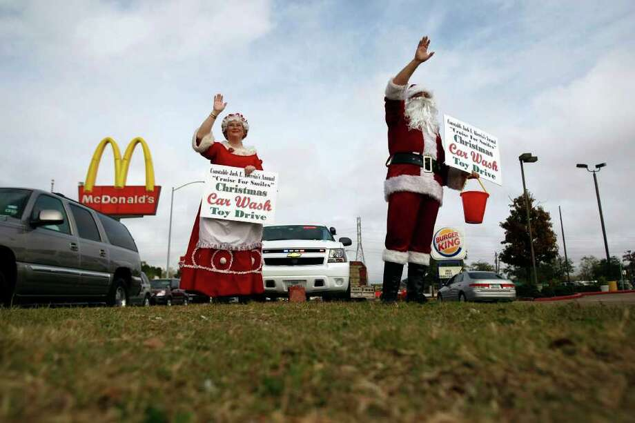 """Santa and Mrs. Claus wave to passing cars during the Constable Jack F. Abercia's Annual """"Cruise for Smiles"""" toy drive along the 3000 block of  Ella Wednesday, Dec. 14, 2011, in Houston. Volunteers collect donated toys and money to give to underprivileged children and their families within Harris County Precinct 1. Photo: Johnny Hanson, Houston Chronicle / Houston Chronicle"""