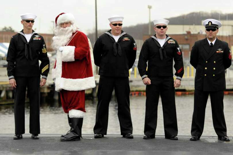 Santa, being played by Chief Petty Officer Gergory Powers, stands atop the hull with other crew memb