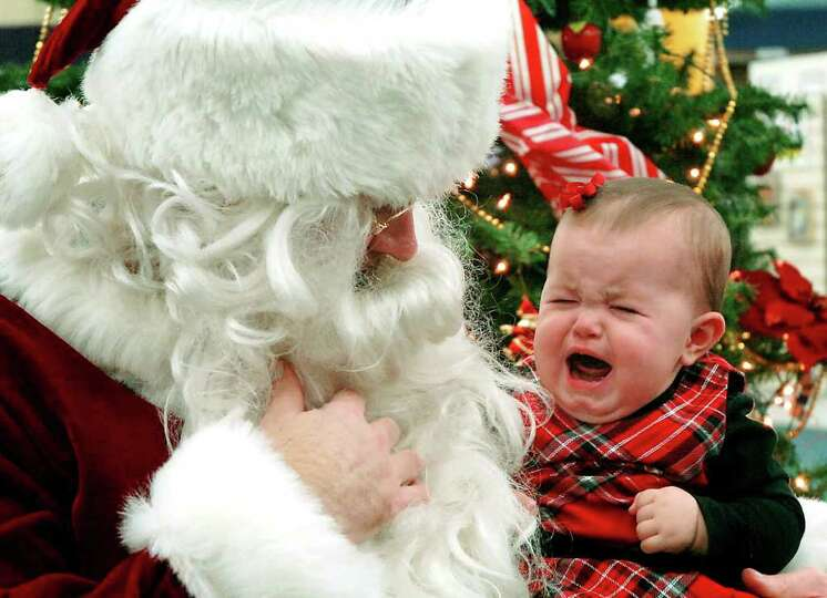 Gillian Kerkman cries while visiting Santa Claus at the Public Library of Enid & Garfield County in