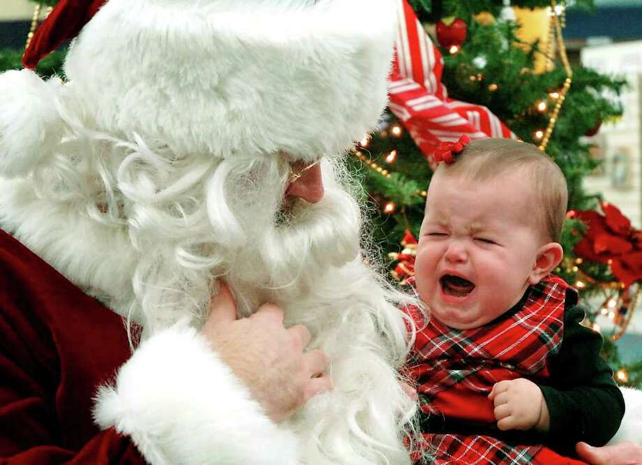 Gillian Kerkman cries while visiting Santa Claus at the Public Library of Enid & Garfield County in Enid, Okla. on Dec.  14, 2011. Photo: Billy Hefton, Associated Press / ENID NEWS & EAGLE