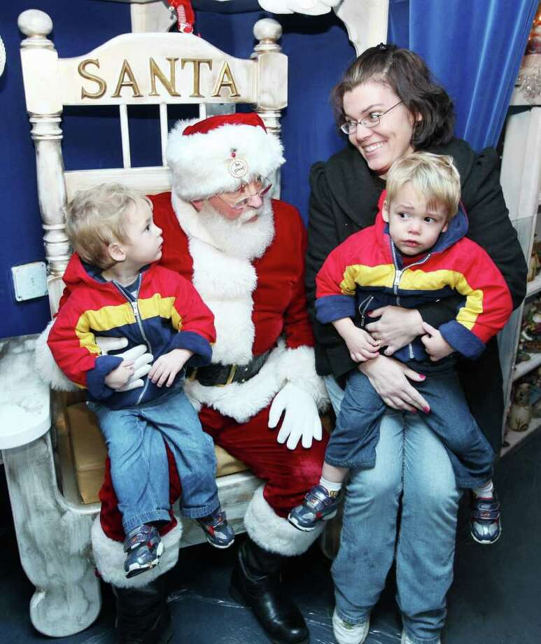 Santa gets a visit from 2-year-old twins Tyler, left, and Ryan Tetidrick, who brought their mom, Bobbie Tetidrick, along to see him on the Kansas City Southern's Holiday Express train in Godfrey, Ill. Photo: John Badman, Associated Press / OUT ILBND and STLPOSTD