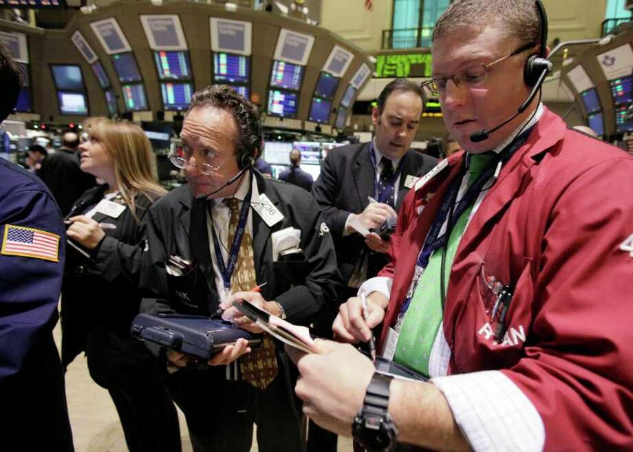 In this Dec. 13, 2011 photo, traders work on the floor of the New York Stock Exchange. Europe's stock markets fell again Wednesday, Dec. 14, 2011 as worries over the ability of governments to get a handle on their debts also pushed the common currency to an 11-month low below $1.30.  (AP Photo/Richard Drew) Photo: Richard Drew