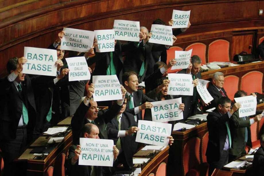 "Northern League Senators hold up placards reading: ""Stop Taxes, Hands off pensions, This austerity package it's a robbery"" , as Italian Premier Mario Monti addresses the Senate, in Rome, Wednesday, Dec. 14, 2011. Italy has had to pay euro-era record high borrowing rates to get investors to lend it euro 3 billion ($3.95 billion) over five years. Wednesday's auction from the Bank of Italy show that the debt-riddled country paid an average yield of 6.47 percent. (AP Photo/Mauro Scrobogna, LaPresse) ITALY OUT Photo: Mauro Scrobogna / PRESL"
