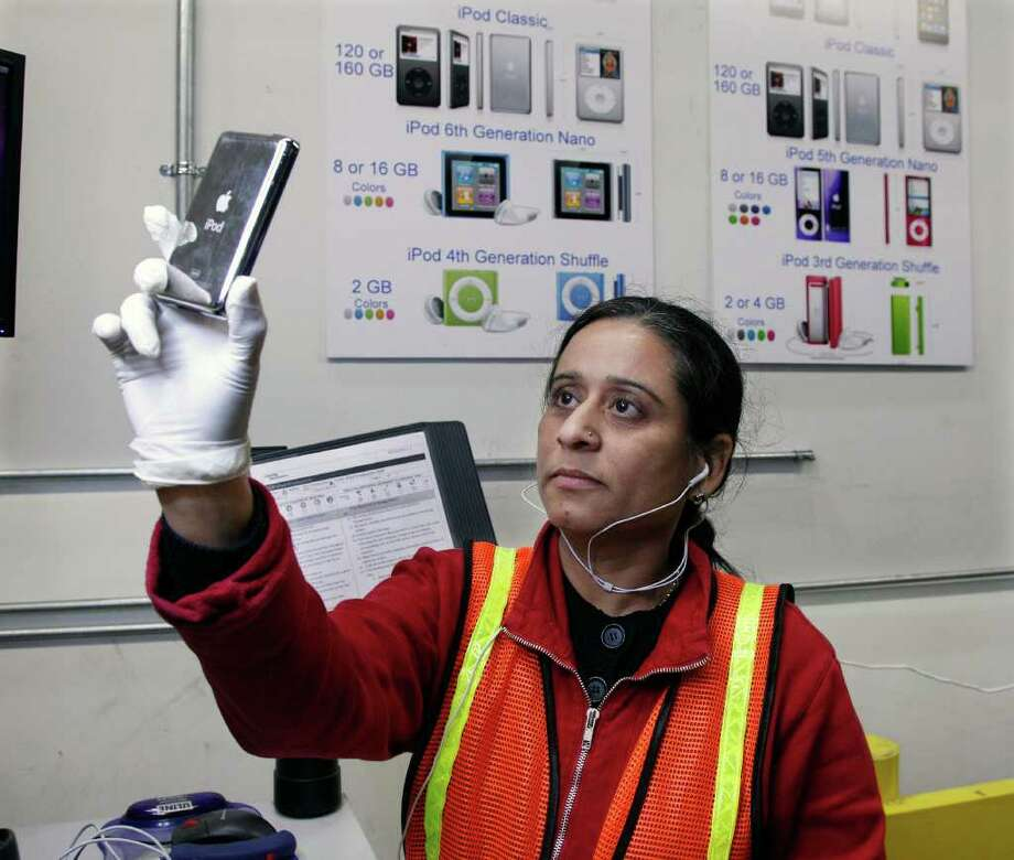 In this Dec. 8, 2011 photo, Kruti Sheth refurbishes iPods at Liquidity Services Inc., in Cranbury, N.J. Liquidation.com has four warehouses full of returned merchandise.   Christmas still is several days away, but shoppers already are suffering from buyers' remorse.  People who rushed to snag discounts on everything from TVs to toys this holiday season are quickly returning those bargains for much-needed cash.  (AP Photo/Mel Evans) Photo: Mel Evans