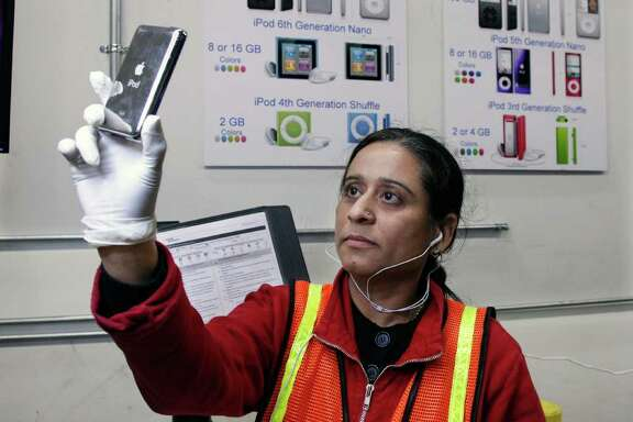 In this Dec. 8, 2011 photo, Kruti Sheth refurbishes iPods at Liquidity Services Inc., in Cranbury, N.J.  Liquidation.com  has four warehouses full of returned merchandise.   Christmas still is several days away, but shoppers already are suffering from buyers' remorse.  People who rushed to snag discounts on everything from TVs to toys this holiday season are quickly returning those bargains for much-needed cash.  (AP Photo/Mel Evans)