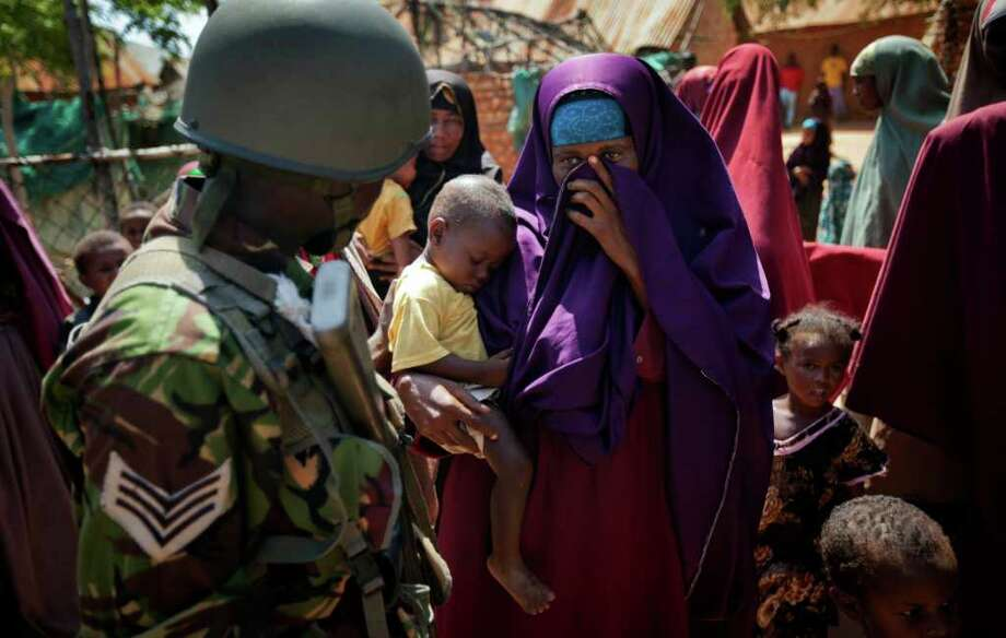 A Somali woman holds her baby who needs treatment, as she talks to a Kenyan army soldier outside a medical clinic where they were examining patients, in the seaside town of Bur Garbo, Somalia, Wednesday, Dec. 14, 2011. The Kenyan military clearly realises that the ultimate success of their mission in Somalia depends on improving the lives of residents there but equally clear is that they did not plan on having to do it all themselves, leaving Somalis in Bur Garbo dependent on handouts from them. Photo: Ben Curtis, Associated Press / AP