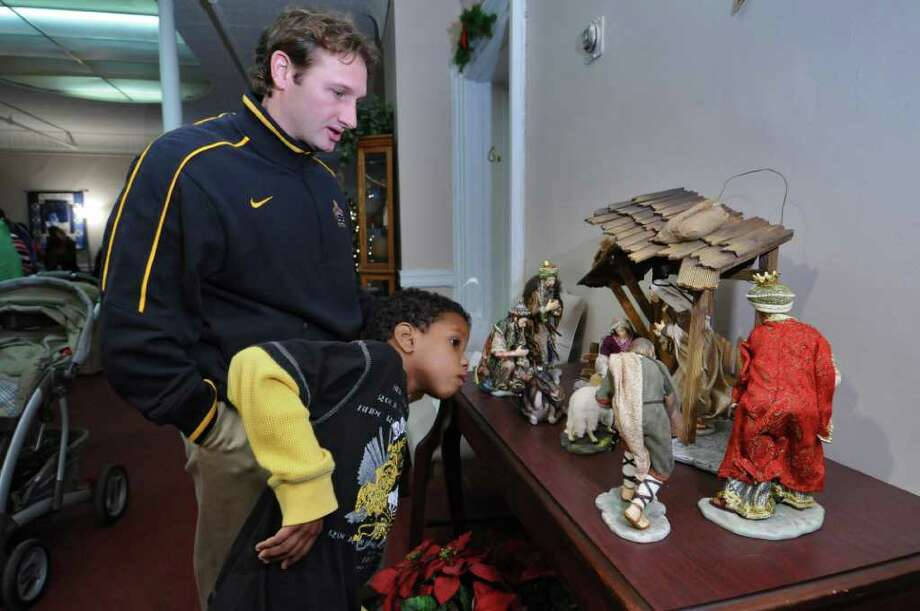 UAlbany assistant football coach Drew Christ talks with Jeremiah Joyner, 6, about a nativity scene on display during the Christmas Blessing Celebration at Koinonia Primary Care on Wednesday Dec. 14, 2011 in Albany, N.Y.  (Philip Kamrass / Times Union ) Photo: Philip Kamrass / 00015744A