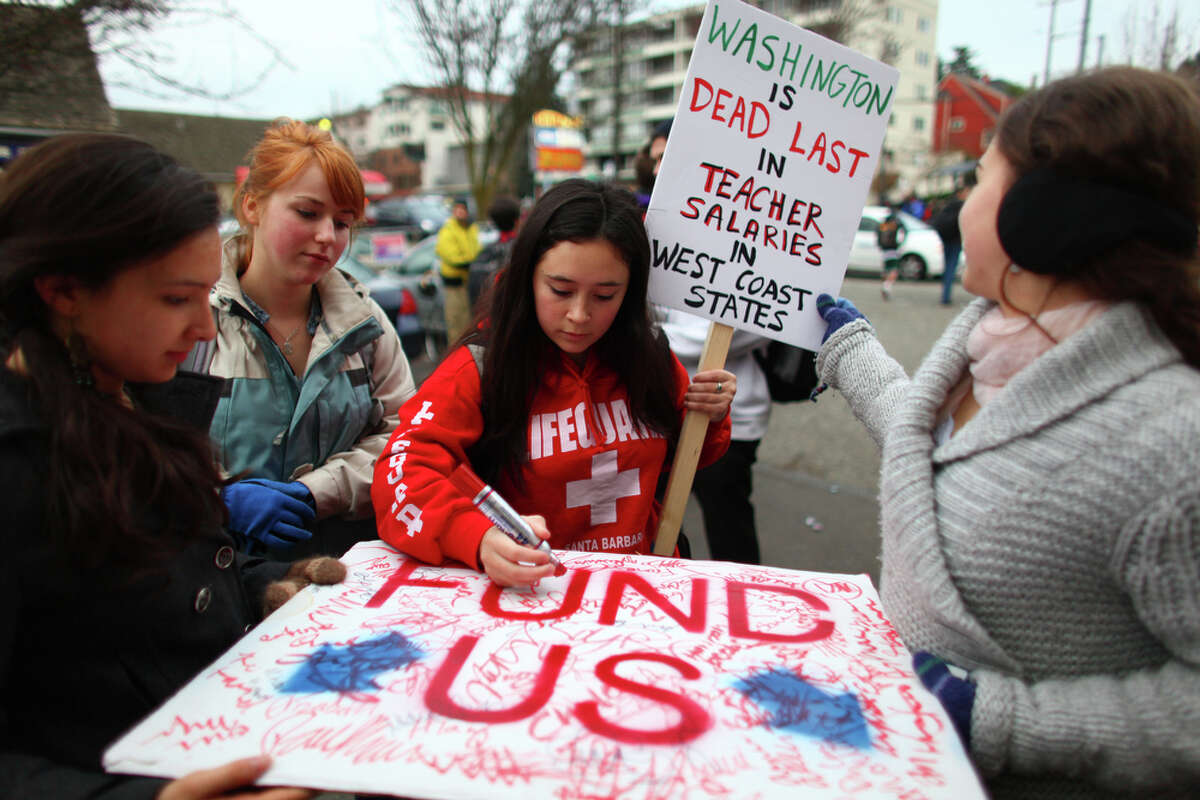 High School students sign a poster to be delivered to House Speaker Frank Chopp during a walkout by Seattle area high school students on Wednesday. The students gathered at Red Square on the UW campus and were marching to protest education cuts proposed by the state government.