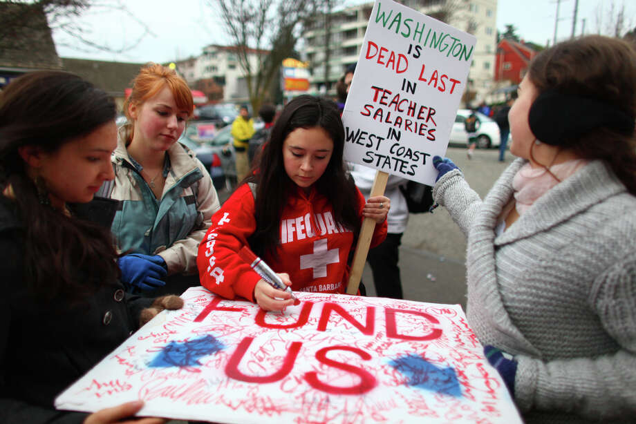 High School students sign a poster to be delivered to House Speaker Frank Chopp during a walkout by Seattle area high school students on Wednesday. The students gathered at Red Square on the UW campus and were marching to protest education cuts proposed by the state government. Photo: JOSHUA TRUJILLO / SEATTLEPI.COM