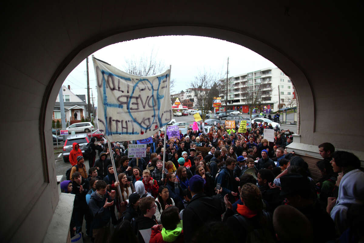 Hundreds of protesters gather outside the old University Heights School building during a walkout by Seattle area high school students on Wednesday, December 14, 2011. The students gathered at the office of State Rep. Frank Chopp to show their opposition to proposed education cuts.