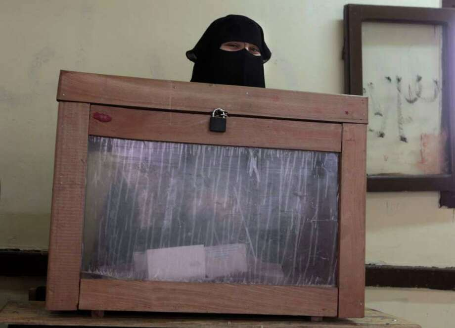An Egyptian official wearing the Niqab  stands next to a ballot box in Giza, Egypt, Wednesday, Dec. 14, 2011. Egyptians in nine provinces voted Wednesday in the second round of the first parliamentary elections since a popular uprising ousted President Hosni Mubarak in February. Photo: Amr Nabil, Associated Press / AP