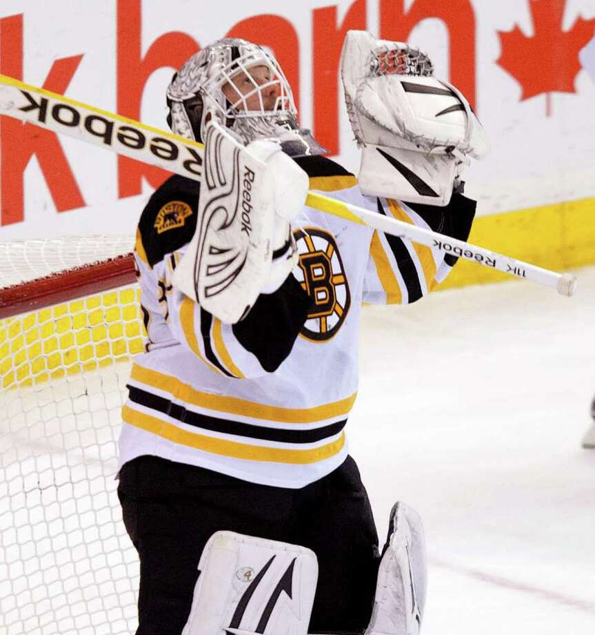 Boston Bruins goalie Tim Thomas celebrates following the team's 5-2 win over the Ottawa Senators in an NHL hockey game, Wednesday, Dec. 14, 2011, in Ottawa, Ontario. (AP Photo/The Canadian Press, Adrian Wyld) Photo: Adrian Wyld