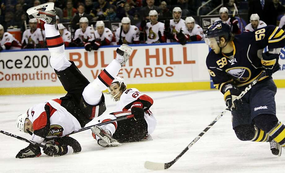 Buffalo Sabres' Paul Szczechura (58) skates with the puck as Ottawa Senators'  Milan Michalek (9), of Czech Republic, collides with Senators' Erik Karlsson (65) during the second period of an NHL hockey game in Buffalo, N.Y., Tuesday, Dec. 13, 2011. (AP Photo/David Duprey) Photo: David Duprey, AP