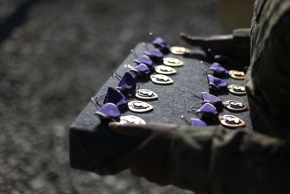 A military aide holds Purple Heart medals that U.S. Sec. of Defense Leon Panetta will award during his visit to the 172nd Infantry Brigade Task Force Blackhawks at a forward operating base in Sharana, Afghanistan,Wednesday, Dec., 14, 2011. (AP Photo/Pablo Martinez Monsivais, Pool)