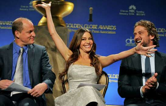 "Actress Sofia Vergara, center, reacts alongside fellow presenters Woody Harrelson, left, and Gerard Butler after she was nominated for Best Performance by an Actress in a Supporting Role in a Series, Mini-Series or Motion Picture Made for Television for ""Modern Family,"" during nominations for the 69th Annual Golden Globe Awards, Thursday, Dec. 14, 2011, in Beverly Hills, Calif. The Golden Globe Awards will be held on Sunday, Jan. 15, 2012, in Beverly Hills, Calif. (AP Photo/Chris Pizzello) Photo: Chris Pizzello"
