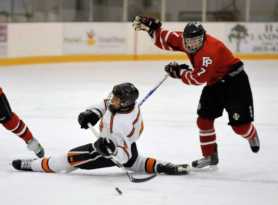 Ridgefield's Jack Christensen falls stretching for the puck while under pressure from Fairfield Prep's William D'Amore during their game at the Winter Garden Ice Arena in Ridgefield on Wednesday, Dec. 14, 2011. Photo: Jason Rearick / The News-Times