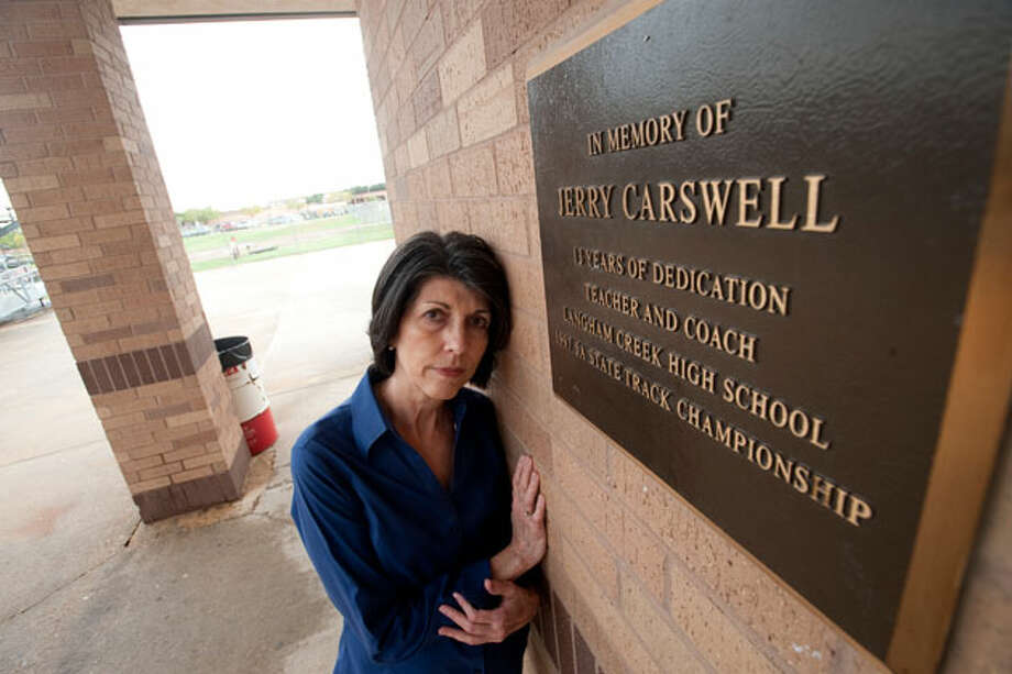 Linda Carswell poses at the Langham High School track by a memorial plaque for her husband. Her lobbying and testimony played a crucial role in the Jerry Carswell Memorial Act, a new informed consent for autopsies bill passed in Texas this year. Photo: Sharon Steinmann, ProPublica / Sharon Steinmann