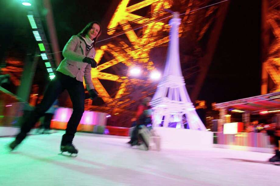 Ice skaters slide on the ice rink set 57 meters (188 feet) above the ground on the Eiffel Tower in Paris, Thursday Dec. 15, 2011. Lodged between two of the tower's immense latticed steel legs, visible in background, the rink is not big at 200 square meters (2,150 square feet), but adds a new dimension to the breathtaking views from Paris' best-known landmark. It will remain open until Jan. 31, 2012. (AP Photo/Francois Mori) Photo: Francois Mori, Associated Press / AP
