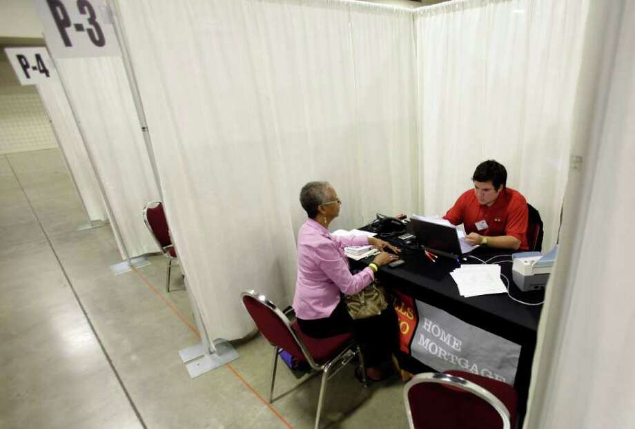 LYNNE SLADKY : ASSOCIATED PRESS GETTING HELP: Burdette Smith, left, talks with Wells Fargo employee Andy Anzaldua of San Antonio during a home preservation workshop Wednesday in Fort Lauderdale, Fla. About 700 people sought assistance to avoid foreclosure. Photo: Lynne Sladky / AP