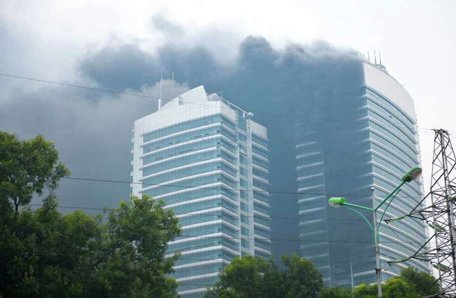 Smoke billows from the twin towers after a fire broke out in the building in Hanoi on December 15, 2011. The fire started from the lower part of the towers which have been newly built by Vietnam's national electricity company EVN, dozens of workers were reportedly injured and transfered to a local hospital,according to local media. AFP PHOTO/STR Photo: STR, Getty / GALAXYCREATIVE