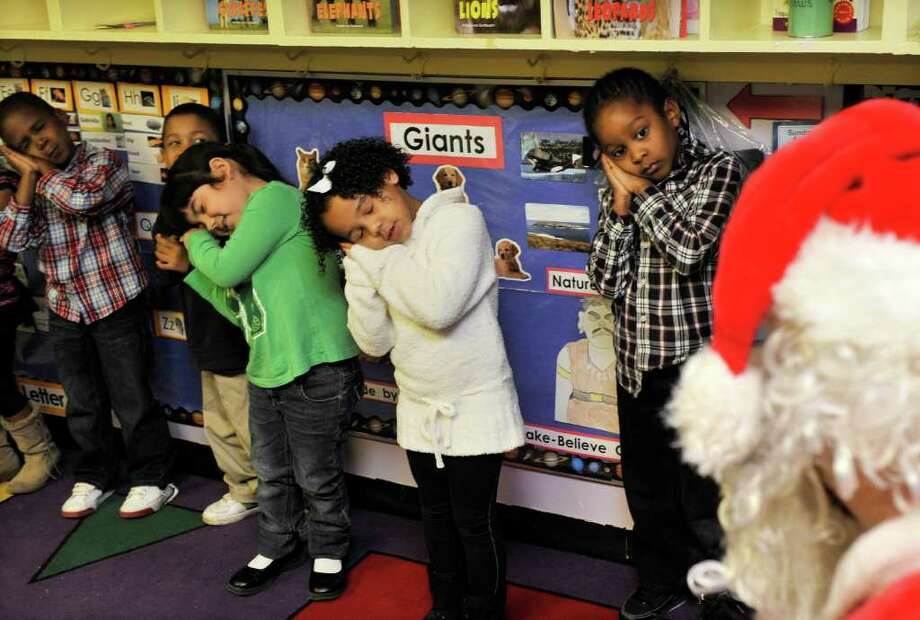 Students SiRod Bethany (from left), Ben Locket, Erin Villarreal, Kalanee Benson and Michael Terry perform a play for Santa, who was at the Montgomery Head Start Center in Windcrest on Thursday, Dec. 15, 2011 distributing gifts provided by the Bexar County Sheriff's Office. Photo: Robin Jerstad, For The Express-News