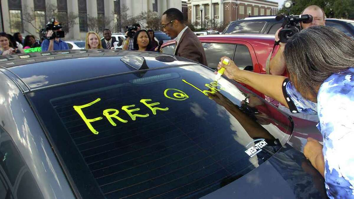 As Calvin Walker, top middle, helps his wife into the car, a message was being written on the rear windshield of their car while they were surrounded by media after leaving the Federal Courthouse Thursday afternoon. U.S. District Judge Ron Clark declared a mistrial in the Calvin Walker federal trial. The 12 person federal jury was deadlocked on reaching a verdict in the case. Walker, 51, right, the Beaumont Independent School District's electrician of record, was accused of defrauding and overbilling the district by nearly $4 million. He was indicted on 37 federal counts in May. Dave Ryan/The Enterprise