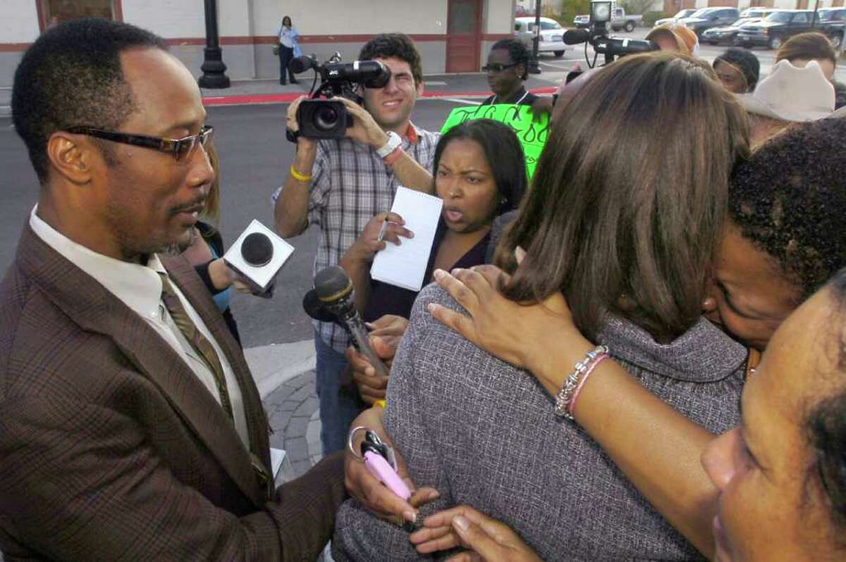While her husband, left, waits and the media tries to question him, Stacy Walker, left, receives hugs from family and friends after she and her husband left the Federal Courthouse Thursday afternoon. U.S. District Judge Ron Clark declared a mistrial in the Calvin Walker federal trial. The 12 person federal jury was deadlocked on reaching a verdict in the case. Walker, 51, right, the Beaumont Independent School District's electrician of record, was accused of defrauding and overbilling the district by nearly $4 million. He was indicted on 37 federal counts in May. Dave Ryan/The Enterprise