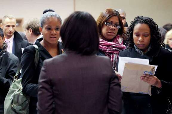 In this Dec. 12, 2011 photo, people talk with a recruiter, center, at a job fair sponsored by National Career Fairs, in New York. The number of people seeking unemployment aid dropped to its lowest level since May 2008 last week, a hopeful sign that layoffs are declining and hiring may pick up.