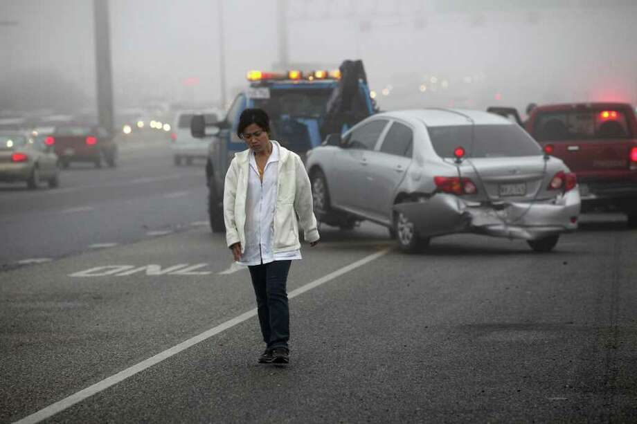 Clay Mu walks away from her car Tuesday, Dec. 13, 2011 as it is towed away from a multi-vehicle wreck on northbound IH-35 between Thousand Oaks Drive and Weidner Road. Low visibility from foggy conditions apparently contributed to the accident that involved between 13-15 vehicles. No major injuries were reported. Traffic backed up on IH-35 to the Walzem Road intersection. Photo: JERRY LARA, San Antonio Express-News / SAN ANTONIO EXPRESS-NEWS