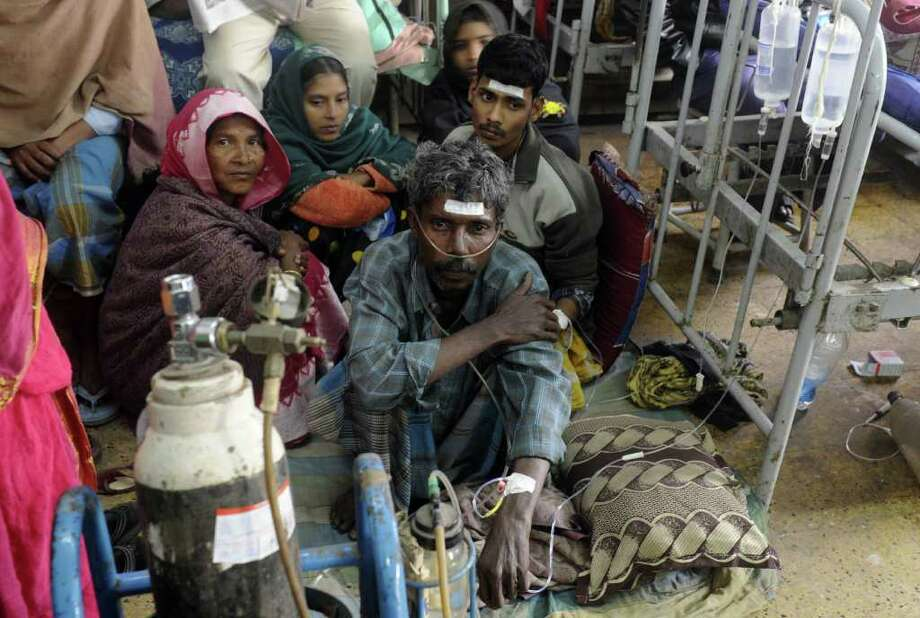 DIBYANGSHU SARKAR : AFP/GETTY IMAGES RECOVERING: Relatives sit with victims Thursday as they receive treatment at a hospital in Diamond Harbour, India, after dozens died and many were sickened by illicit liquor south of Kolkata. Officials said the booze had been spiked with methanol. Photo: DIBYANGSHU SARKAR / AFP
