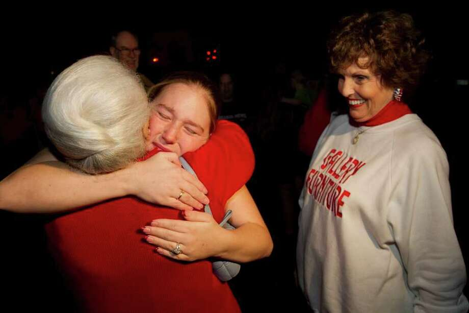 BRETT COOMER PHOTOS : CHRONICLE A HAPPY DAY: Tina Robertson, center, embraces Nana White, who helped her family get free furniture from Gallery Furniture, represented by Georgia Ann Spears, right. The Robertsons lost their home last summer in  the Magnolia wildfires. Photo: Brett Coomer / © 2011 Houston Chronicle