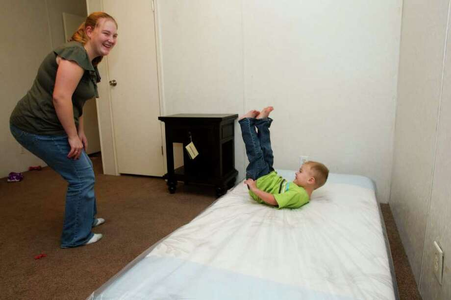 Tina Robertson, left, smiles as her son, Garrett, jumps on his new bed that was given to their family as part of the annual Gallery Furniture Giveaway in Magnolia. The Robertson family lost their home last summer during the Magnolia wildfires, as Jerry Roberston, a Tri-County firefighter, was out battling the blaze. Photo: Brett Coomer, Houston Chronicle / © 2011 Houston Chronicle