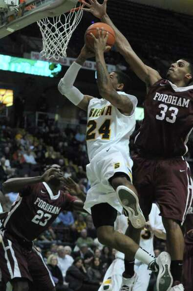 Siena's Davonte Beard is defended by Fordham's Chris Gaston, right,  during the second half of Siena