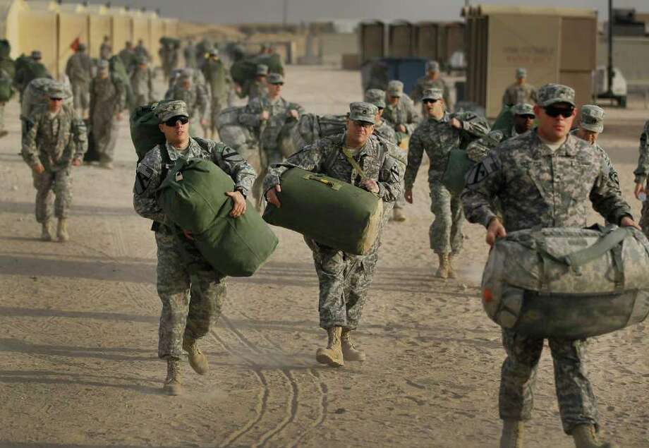 Joe Raedle: Getty Images ONE LAST HIKE:  U.S. soldiers from the 2-82 Field Artillery, 3rd Brigade, 1st Cavalry Division, carry their bags to waiting trucks Thursday before boarding buses for a flight home to Fort Hood, Texas. It was one of the last American combat units to exit from Iraq, flying out of Camp Virginia, near Kuwait City, Kuwait. Photo: Joe Raedle / 2011 Getty Images