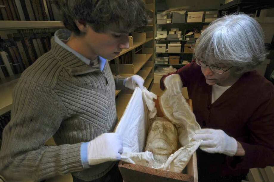 Annette LeClair, librarian and head of technical services for Union College's Schaffer Library, right, and digital projects assistant Matthew Connolly, left, unwrap a plaster death mask from 1911 of Union College graduate John Bigelow, in the Special Collections storage area of the library on Tuesday Dec. 13, 2011 in Schenectady, N.Y.  Bigelow was a founder of the New York Public Library, consul general to Paris for President Abraham Lincoln and a friend to Charles Dickens and other literary figures. An exhibit marking the centennial of his death begins in the library on Dec. 19. (Philip Kamrass / Times Union ) Photo: Philip Kamrass / 00015747A