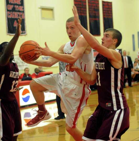 Watervliet's Antoine Johnson, left, and teammate Griffin Kelly, right, defend  against Albany Academ