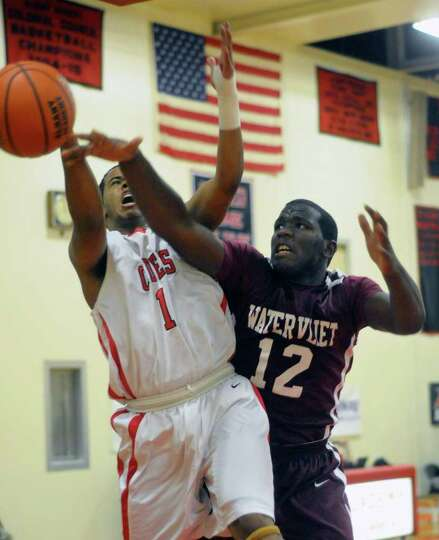Albany Academy's Darrien White (1) and Watervliet's Antoine Johnson (12) battle for the ball during