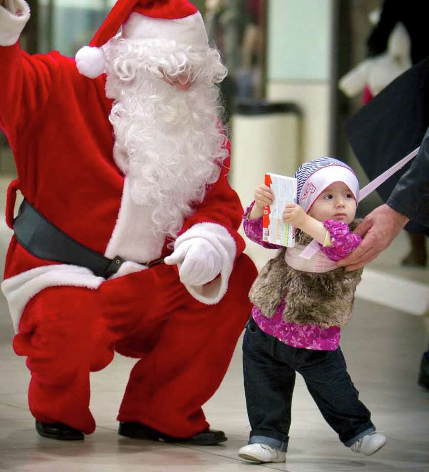 A man tries to persuade a small child not to get away from a person dressed as Santa Claus after the child receives a chocolate bar in an attempt to photograph them together at a shopping mall in Bucharest, Romania. Photo: Vadim Ghirda, Associated Press / AP