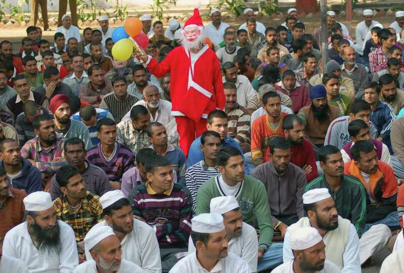 An Indian youth dressed up as Santa Claus walks past gathered inmates during a pre-holiday event at